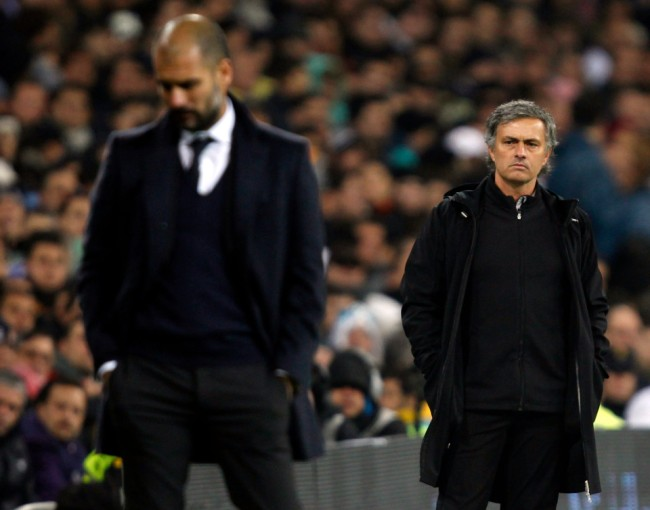 Real Madrid's coach Jose Mourinho looks at Barcelona coach Pep Guardiola after Xavi Hernandez goal during their Spanish first division soccer match, the Clasico, at the Santiago Bernabeu stadium in Madrid